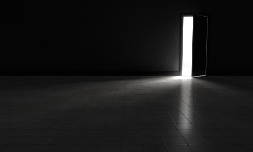 An open door with bright light streaming into a very dark room